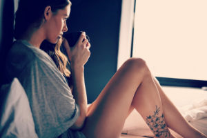 woman with tattoo on leg looks sad while holding mug of tea in bed