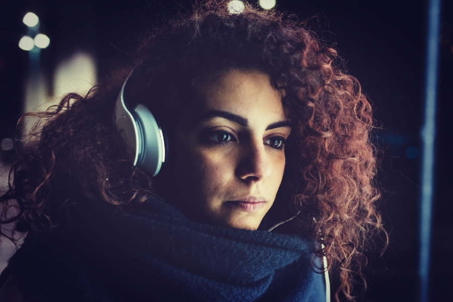 woman with headphones looks into distance