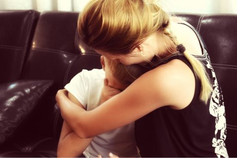 a mother comforts her son
