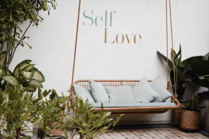lovely porch area with wicker swing, plants and the words Self Love on the wall