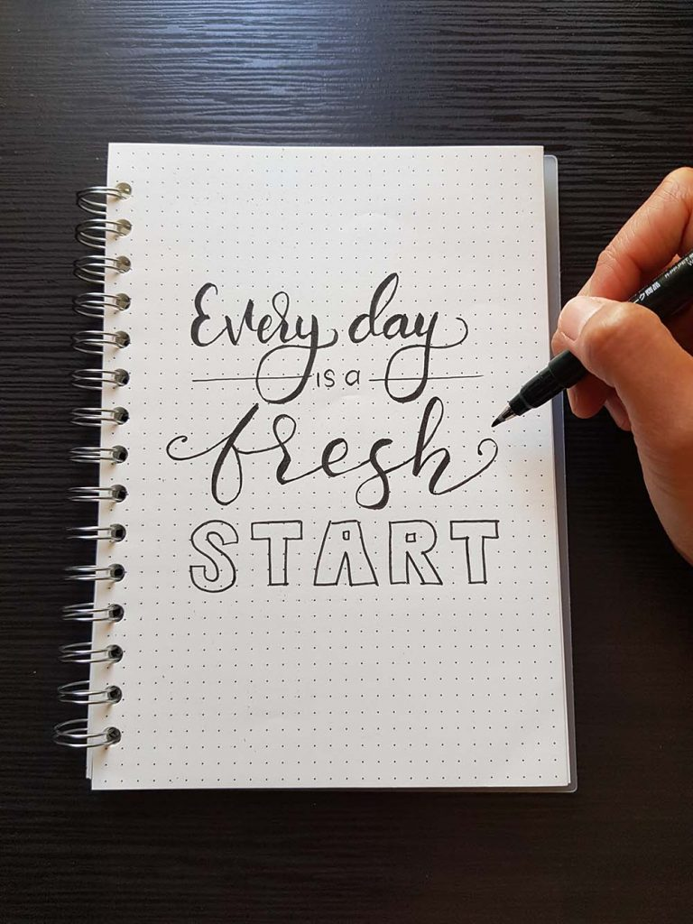 a hand writes in a notebook: Every day is a fresh start