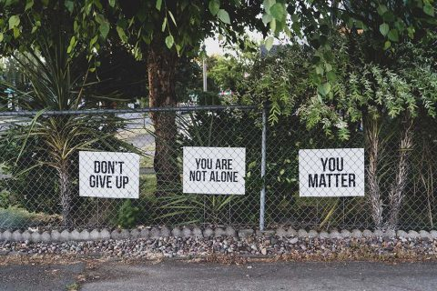 a fence displays encouraging messages on signs