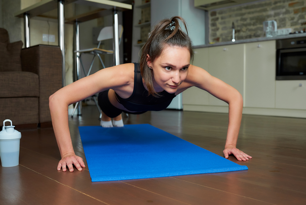 A sporty skinny girl in a black workout tight suit is doing push-ups to warming up pectoral muscles, triceps, and shoulders on the blue yoga mat at home. A woman is practicing exercises for the chest.