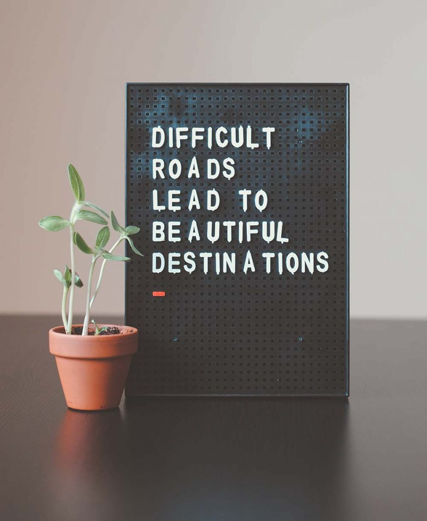 a letterboard displays the message: Difficult roads lead to beautiful destinations
