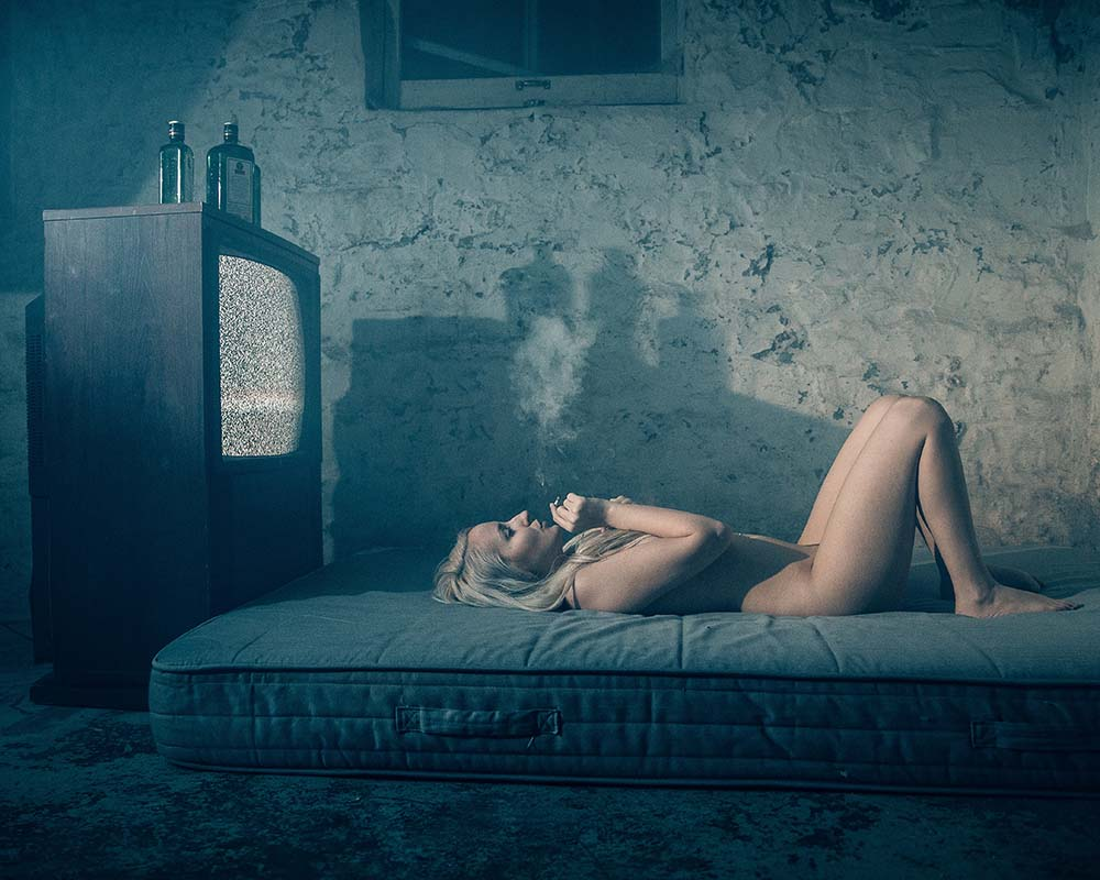 nude woman smoked on a bed while alcohol bottles sit on a tv behind her