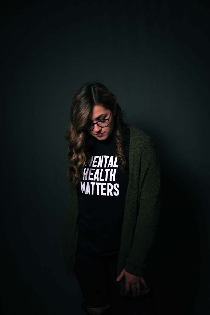 a woman wears a shirt that reads: Mental Health Matters