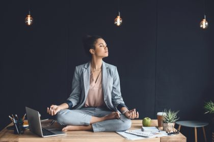 young black woman sits on her desk meditating