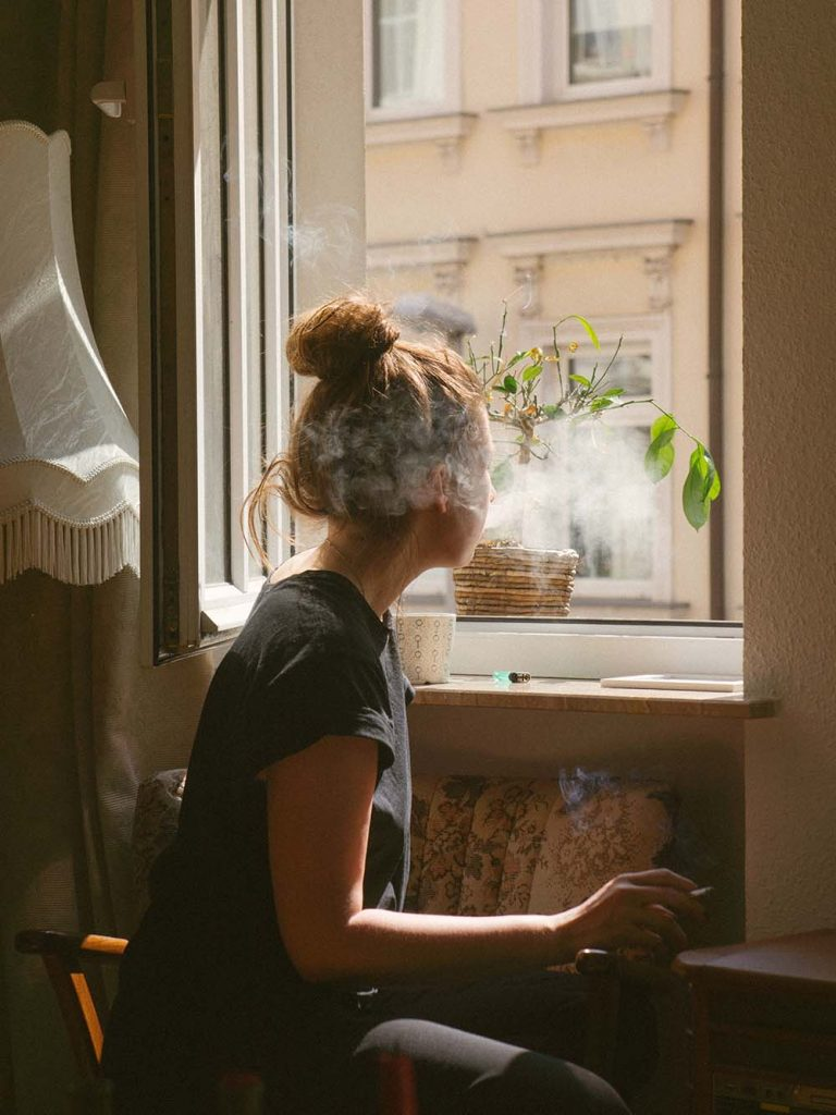 a woman sits in front of a window smoking